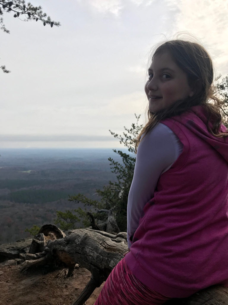A young girl takes in the view from atop Crowder's Mountain