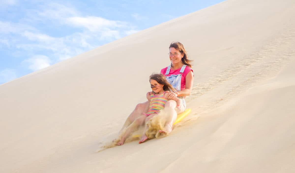 family sledding down a sand dune